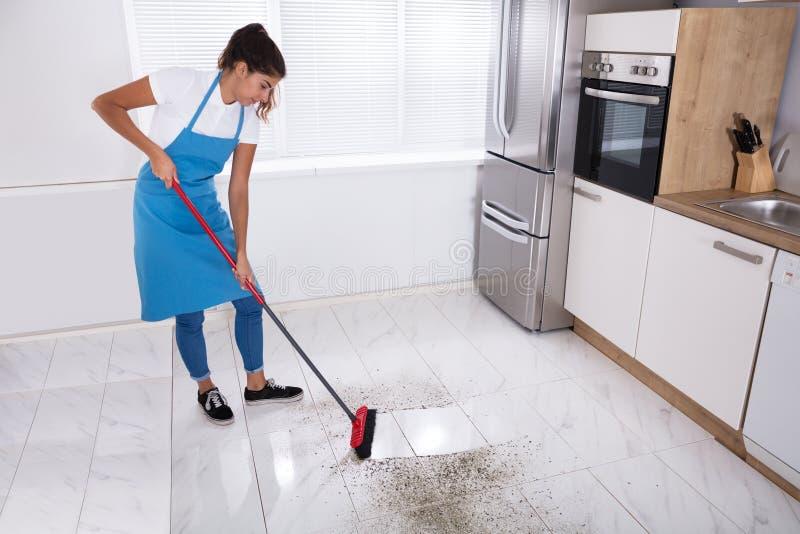 Hausgehilfin-Reinigungs-Boden mit Besen lizenzfreies stockfoto