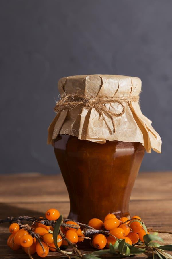 hausgemachte Herstellung von Konserven und Beeren, Konfitüre, Pavidlo aus reifen Früchten des Seeschuckthorns in einem Glasgefäß  lizenzfreies stockbild