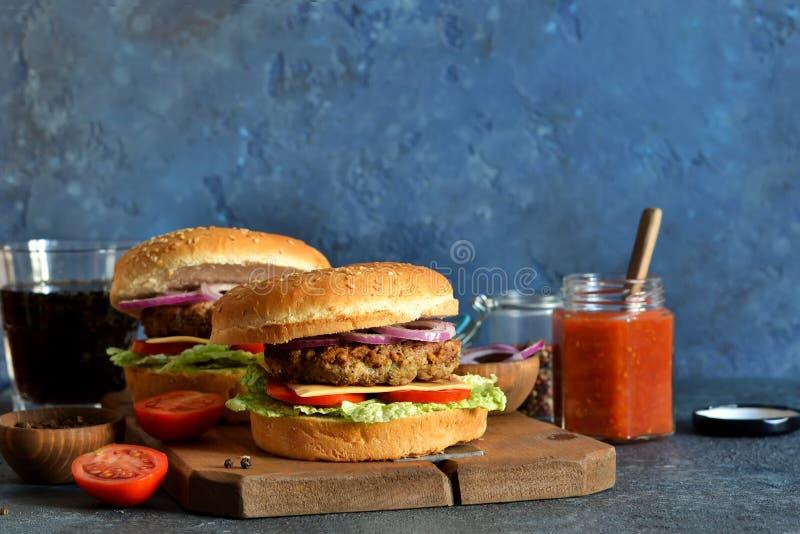 hausgemachten Hamburger mit Rind, Käse und Soße auf einem Betonboden horizontal stockfotografie