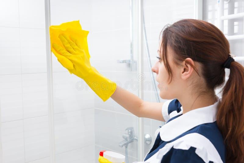 Haushälterin, welche die Glasduschkabine säubert stockfoto