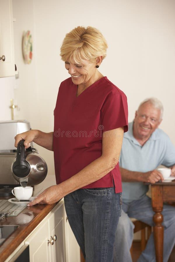 Haushaltshilfe, die Tasse Tee mit älterem Mann in der Küche teilt stockfotografie