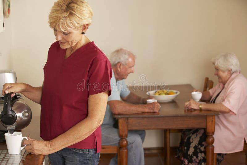 Haushaltshilfe, die Tasse Tee mit älteren Paaren in der Küche teilt stockbilder