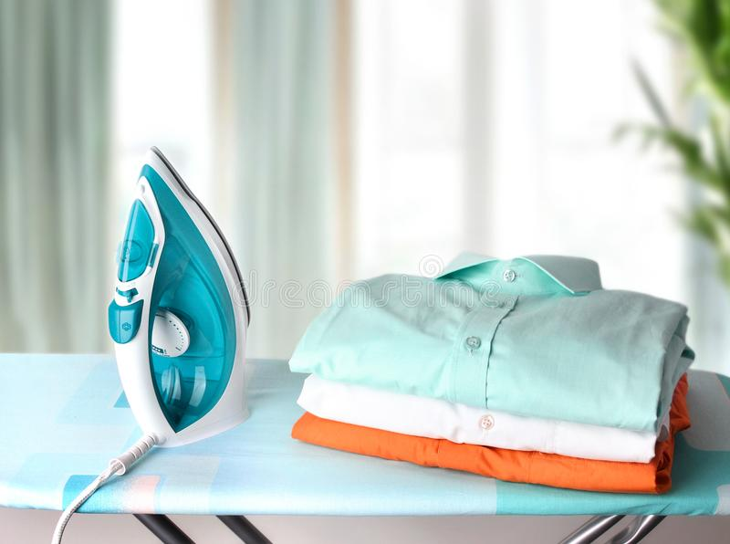 Haushaltskonzept Bügelbrett mit Kleidung lizenzfreies stockfoto
