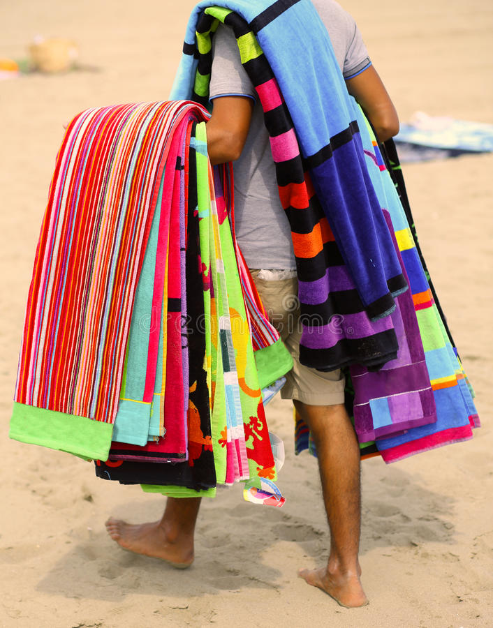 Hausierer von Tüchern und von Badetüchern auf dem Strand im Sommer stockfoto
