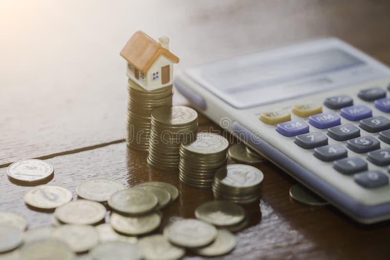 Hausmodell auf Münzen stapelt mit Taschenrechner als Hintergrund Conce lizenzfreies stockfoto