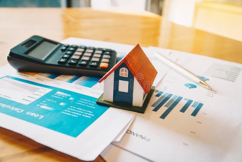 Hausmodell, Taschenrechner und Finanzdiagramm auf Holztisch Investition zu kaufendem Eigentumskonzept lizenzfreies stockfoto