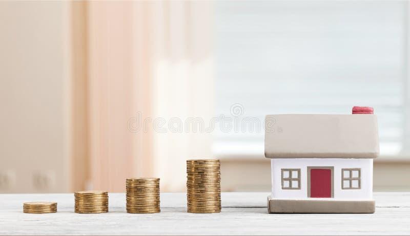 Hausmodell und goldene Münzenstapel lizenzfreies stockfoto
