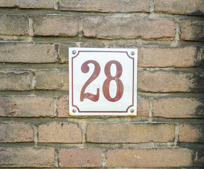 Hausnummer 28 achtundzwanzig braune Zahlen auf einem weißen Plattenbetrug lizenzfreies stockbild