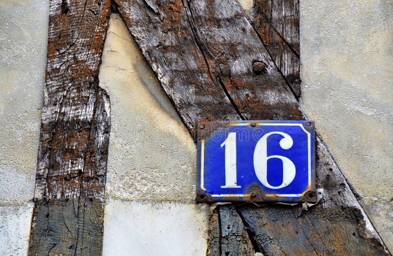 Hausnummer 16 auf antiker rustikaler Wand, altes, rostiges Emailleschild stockfotos