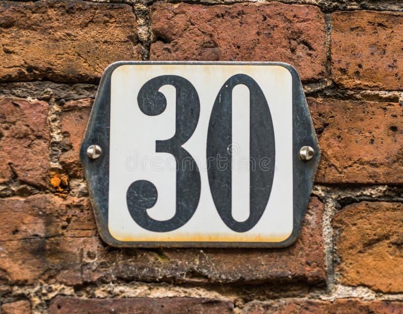 Hausnummer 30 auf traditioneller niederländischer Backsteinmauer stockfotografie