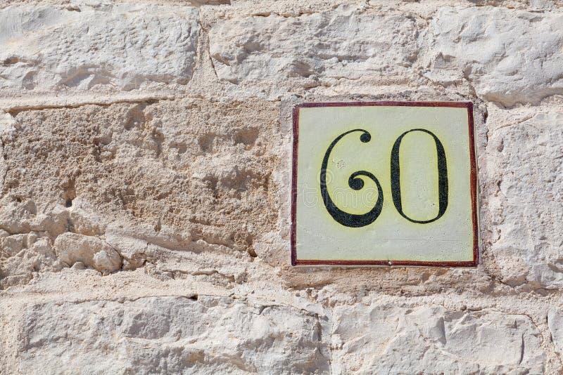 Hausnummer sechzig als quadratische Fliese lizenzfreie stockfotos
