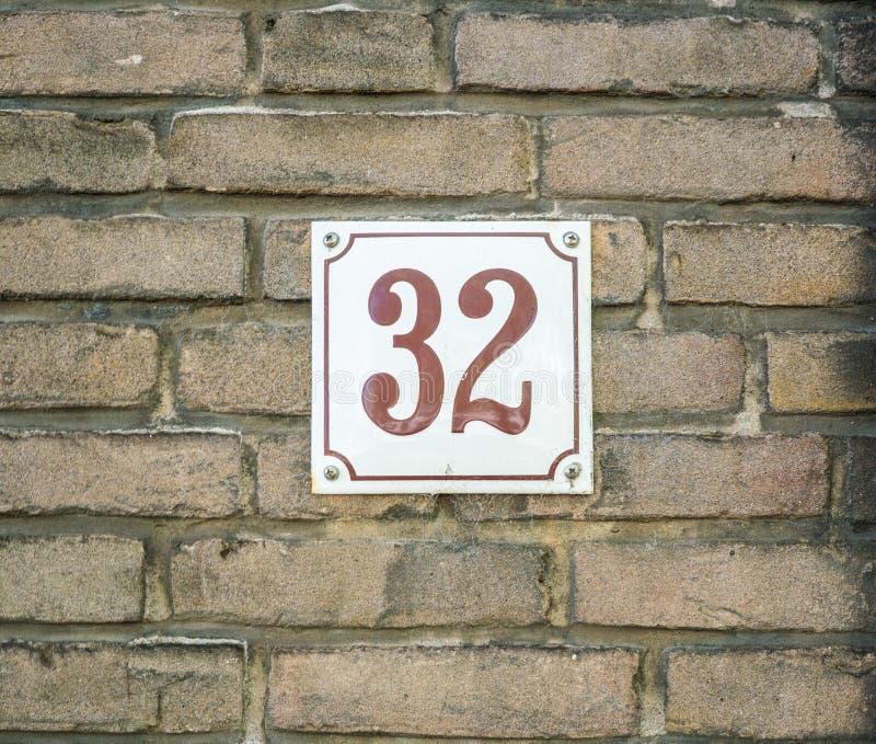 Hausnummer 32 zweiunddreißig braune Zahlen auf einem weißen Platte const lizenzfreie stockfotos