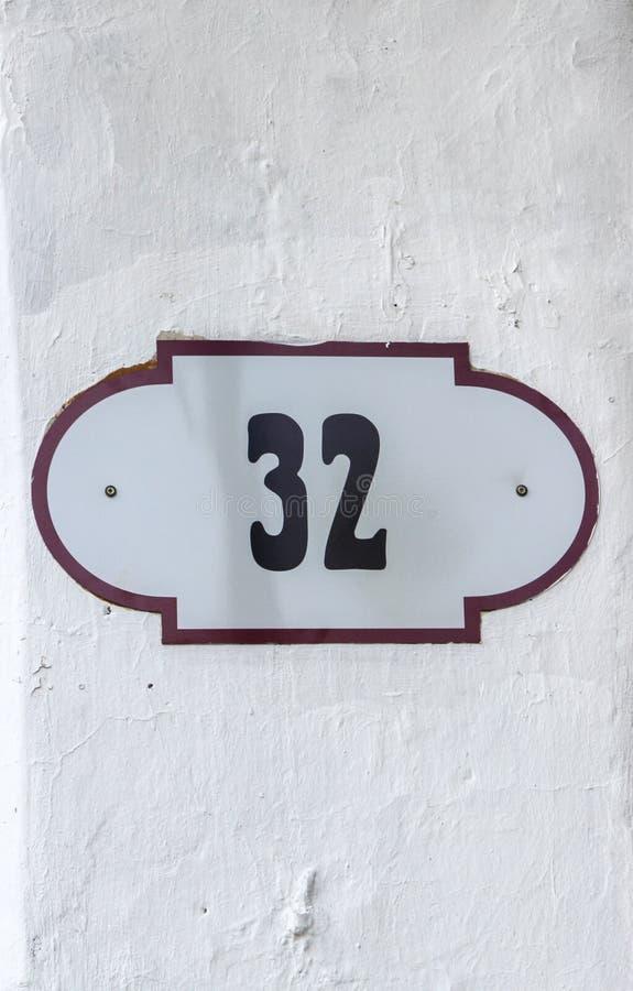 Hausnummer 32 zweiunddreißig Schwarze Beschriftung auf einer weißen Metallplatte mit braunem Rand lizenzfreies stockbild