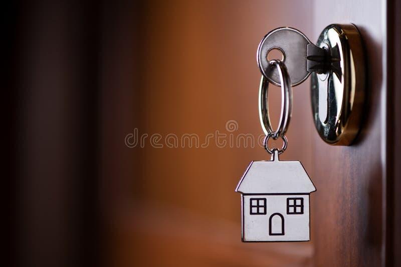 Hausschl?ssel auf einem geformten silbernen Schl?sselring des Hauses im Verschluss einer Einstiegst?r lizenzfreies stockbild