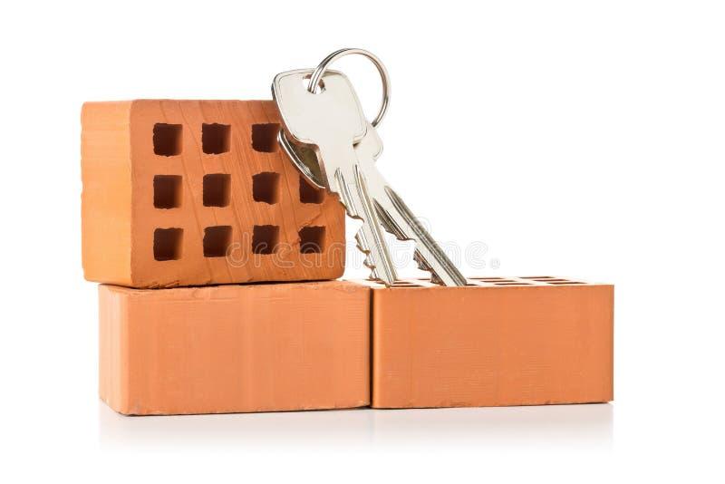 Hausschlüssel auf Ziegelsteinen über weißem Hintergrund - Hauseigentümer, Immobilien oder Wohnungsbaukonzept lizenzfreies stockfoto