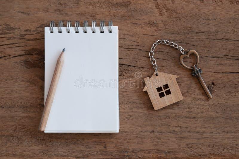 Hausschl?ssel mit Hauptschl?sselring, leerem Notizbuch und Bleistift auf wei?em h?lzernem Tabellenhintergrund stockfotografie