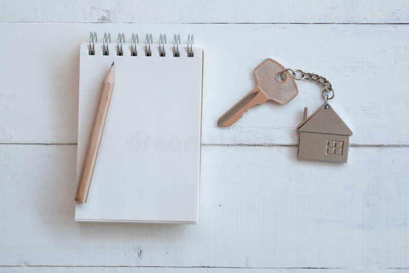 Hausschl?ssel mit Hauptschl?sselring, leerem Notizbuch und Bleistift auf wei?em h?lzernem Tabellenhintergrund stockfoto