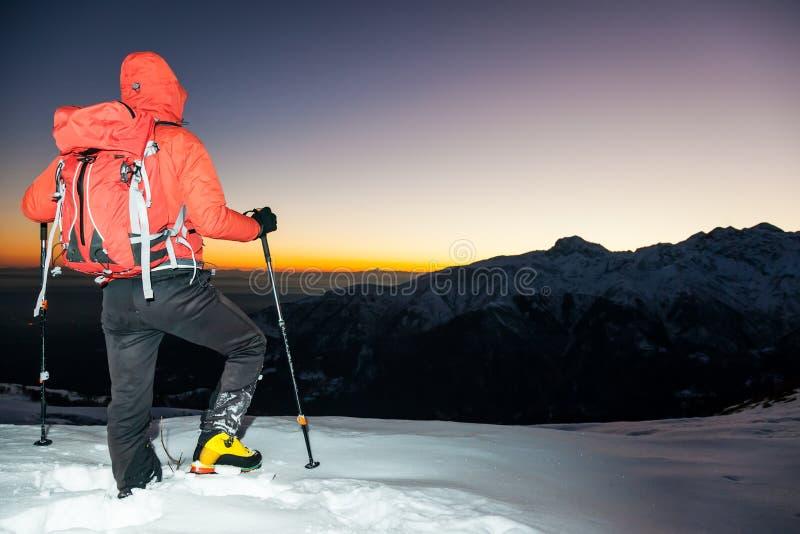 Hausse d'hiver : l'homme se tient sur une arête neigeuse regardant le coucher du soleil photo stock