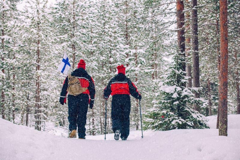 Hausse d'hiver Les touristes trimardent dans le beau paysage d'hiver de forêt couverte de neige photo libre de droits