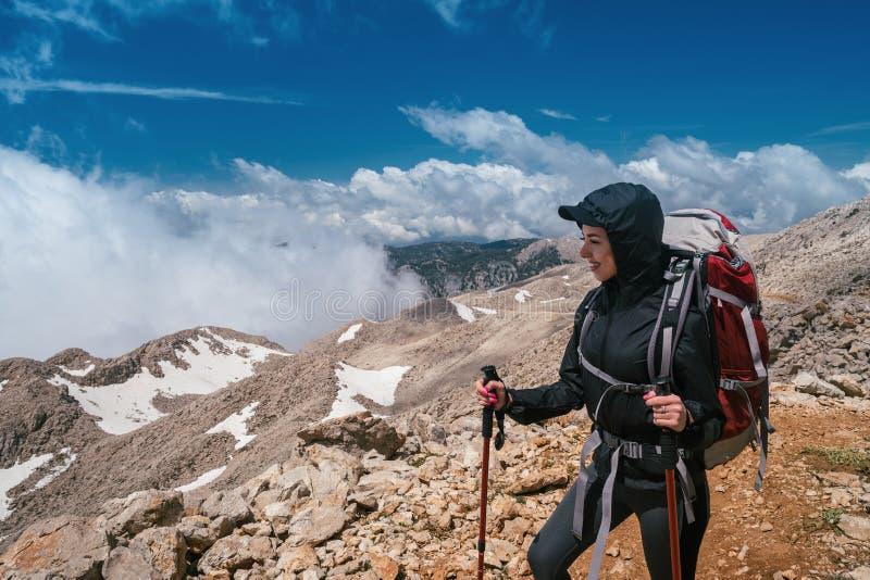 Hausse dans les montagnes Une fille se tient dans la perspective de hautes montagnes et d'un beau ciel bleu photo stock