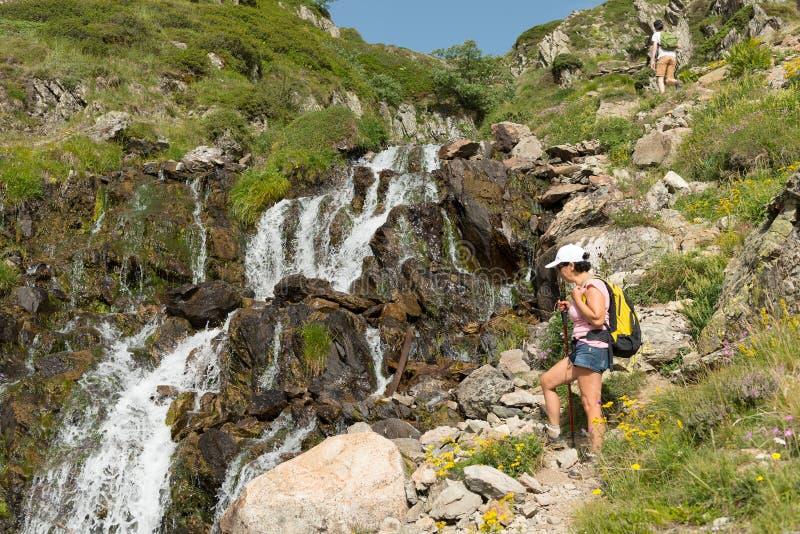 Hausse de la femme à côté de la cascade dans les montagnes photos libres de droits
