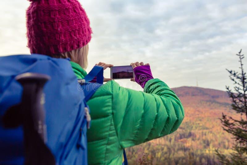 Hausse de la femme avec le sac à dos prenant la photo avec le smartphone photo stock