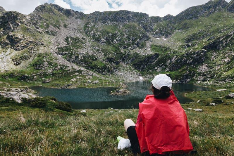 Hausse de la fille prenant le repos et détendant devant un lac a de montagne photos libres de droits