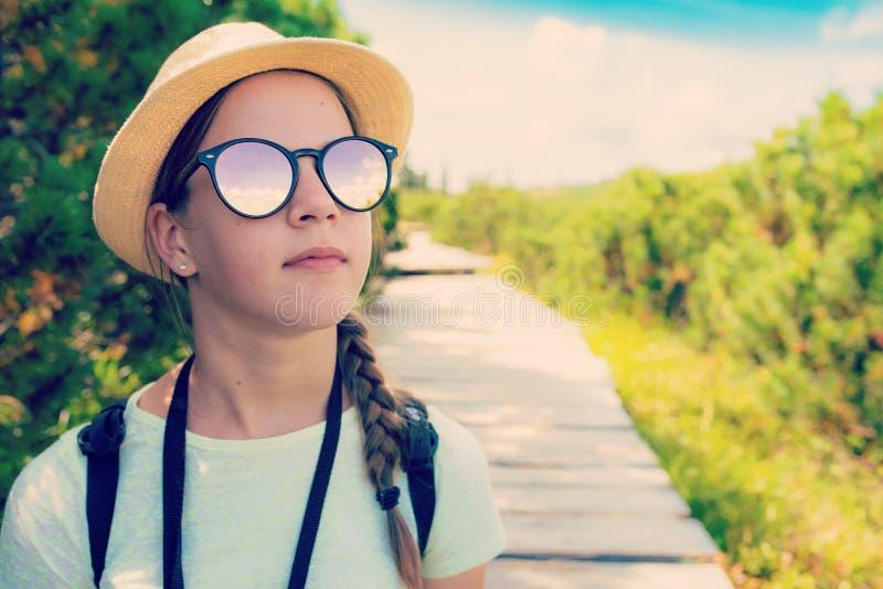 Hausse de la fille de touristes adolescente dans des lunettes de soleil dans les montagnes photos libres de droits