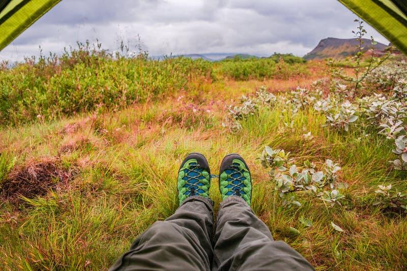 Hausse des bottes, de la tente et de la toundra volcanique au coucher du soleil sur l'Islande photos stock