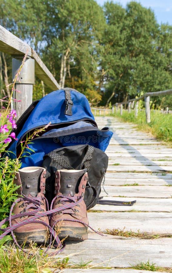 Hausse des bottes et du sac à dos sur un chemin image stock