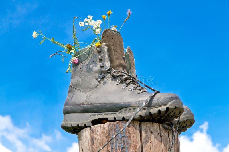 Hausse des bottes sur un enjeu en bois photographie stock libre de droits