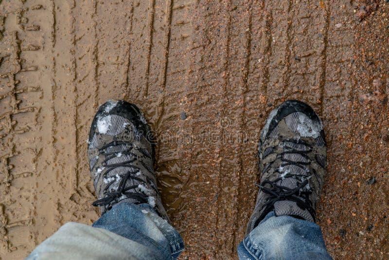 Hausse des chaussures se tenant dans le chemin de boue photo stock