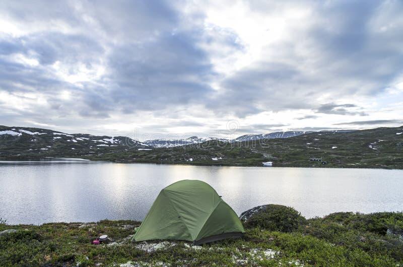 Hausse du fond Tente de camping sur le rivage de lac en montagnes de la Norvège images stock