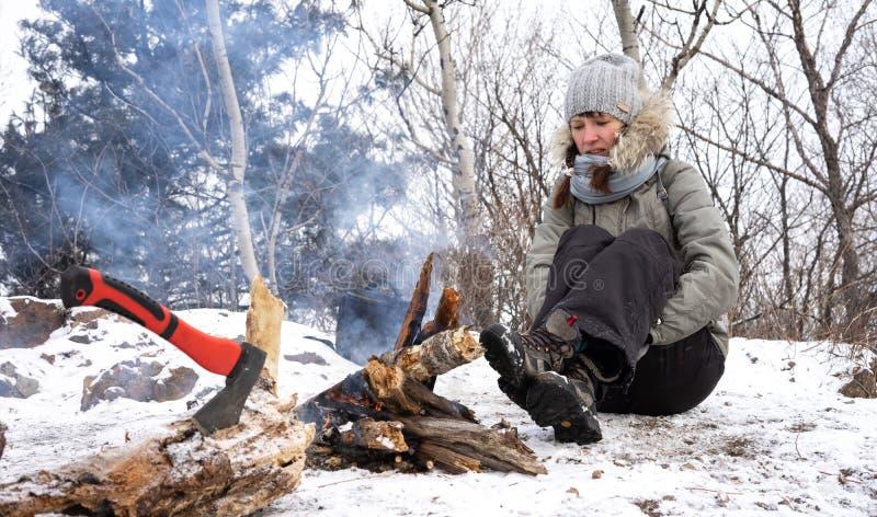 Hausse : Une fille dans un chapeau gris sur une halte se chauffe par le feu en hiver dans les montagnes photos stock