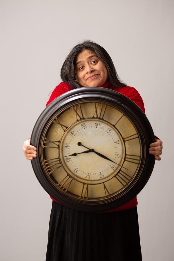Haussements d'?paules hispaniques de femme tout en tenant l'horloge en Front Of Her image libre de droits
