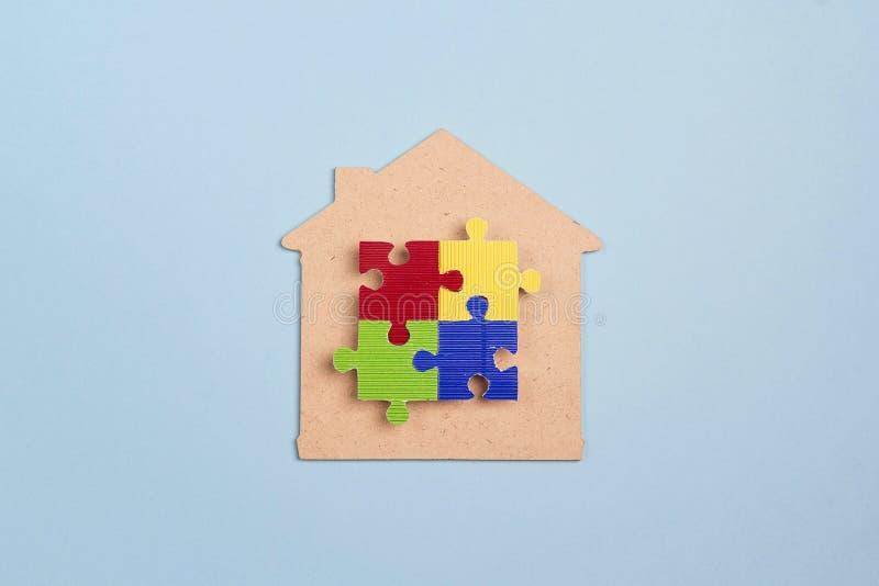 Haussymbol mit buntem Puzzlespiel auf einem blauen Hintergrund Autismusbewusstseinstag stockfotos