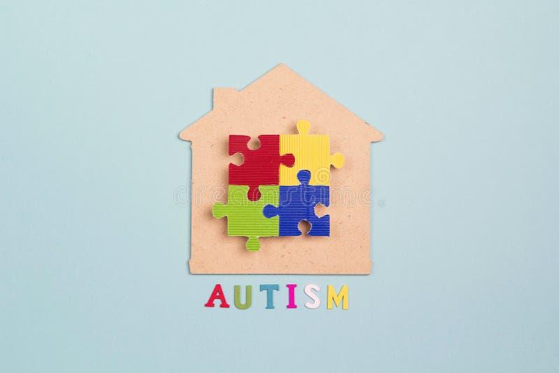 Haussymbol mit buntem Puzzlespiel auf einem blauen Hintergrund Autismusbewusstseinstag stockfoto