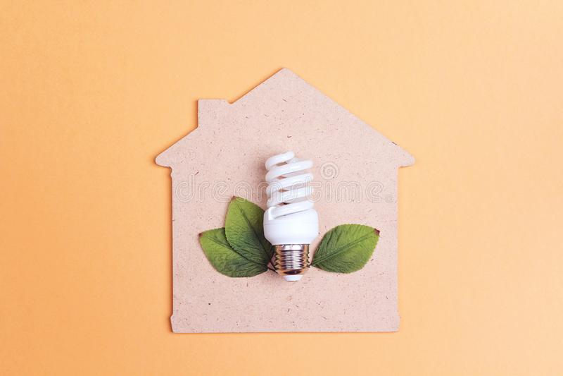 Haussymbol mit energiesparender Glühlampe Außer Energiekonzept stockbilder