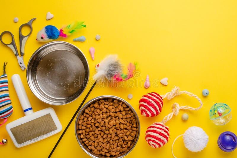 Haustier, Katze, Nahrung und Zusätze der Katze flache Lage, mit Raum für Entwurf, auf gelbem Hintergrund lebend lizenzfreies stockbild