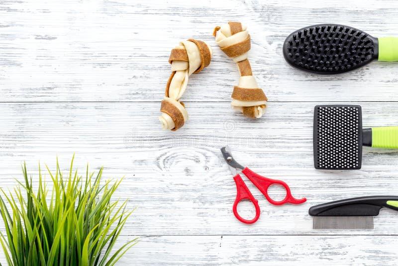 Haustierpflege- und Pflegenwerkzeuge mit Bürsten auf weißem hölzernem Draufsichtraum des Hintergrundes für Text lizenzfreie stockfotografie