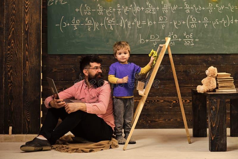 Hausunterricht Lehrer, der das Kind abwischt Tafel betrachtet Lächelnder Mann in den Gläsern, die auf dem Boden und dem Kind mit  stockfotografie