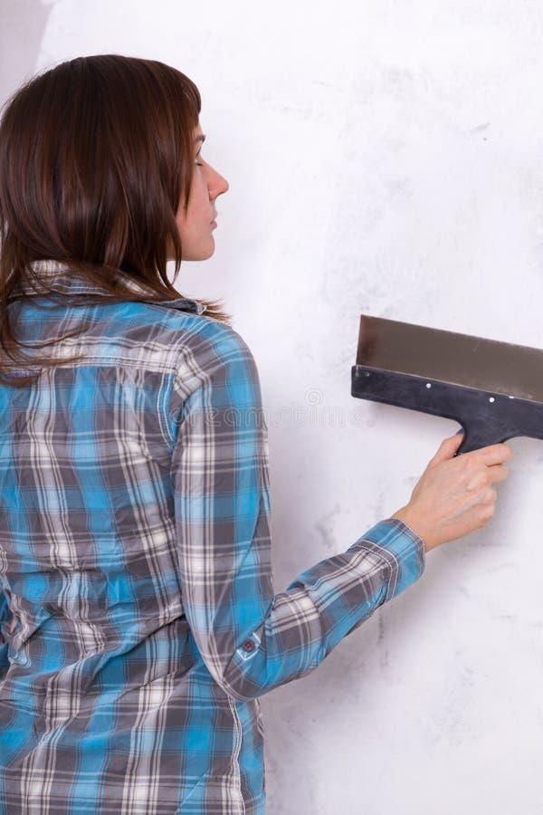 Hausverbesserung durch Arbeitnehmerin setzt Deckschicht des Stucks lizenzfreie stockfotografie