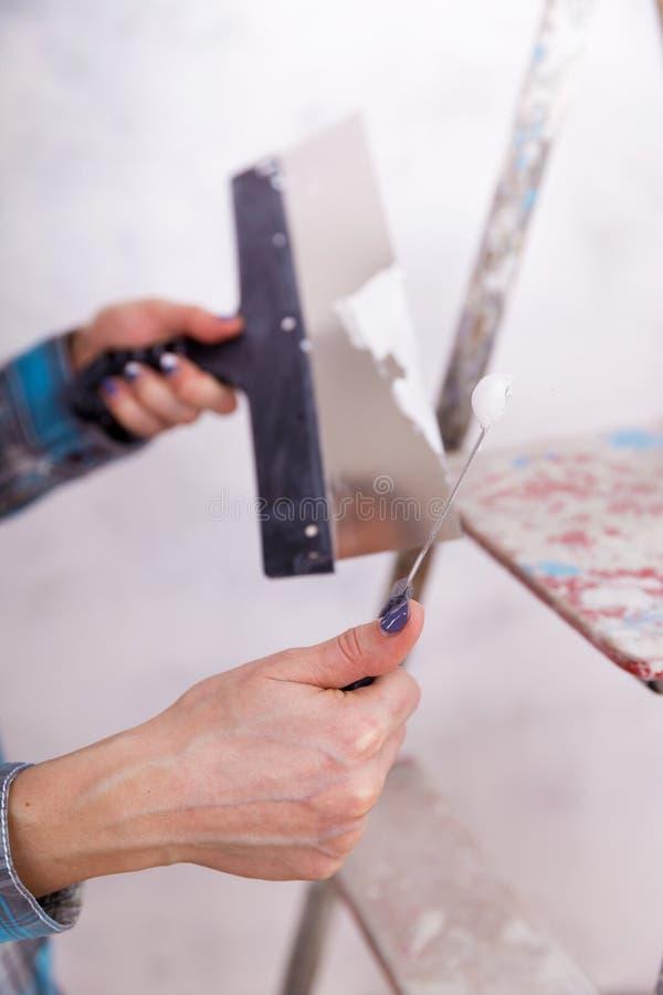 Hausverbesserung durch Arbeitnehmerin setzt Deckschicht des Stucks lizenzfreies stockbild