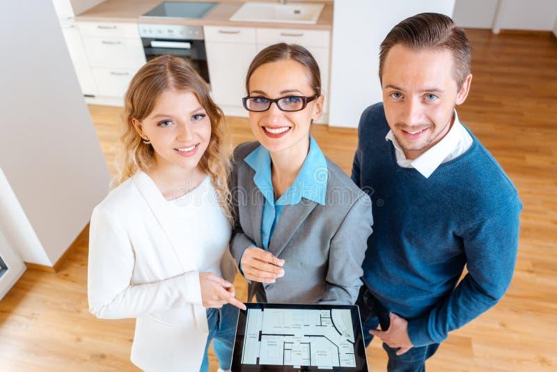 Hausvermittler und -kunden in der neuen Wohnung, die Kamera untersucht stockbild