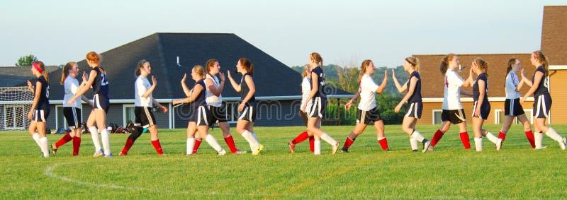 Haut-fives pour tous à l'extrémité d'un jeu de football de filles photo stock