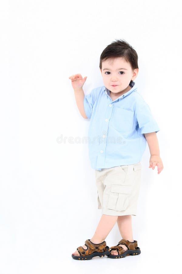 Haut garçon principal d'enfant en bas âge restant contre le mur blanc photos libres de droits