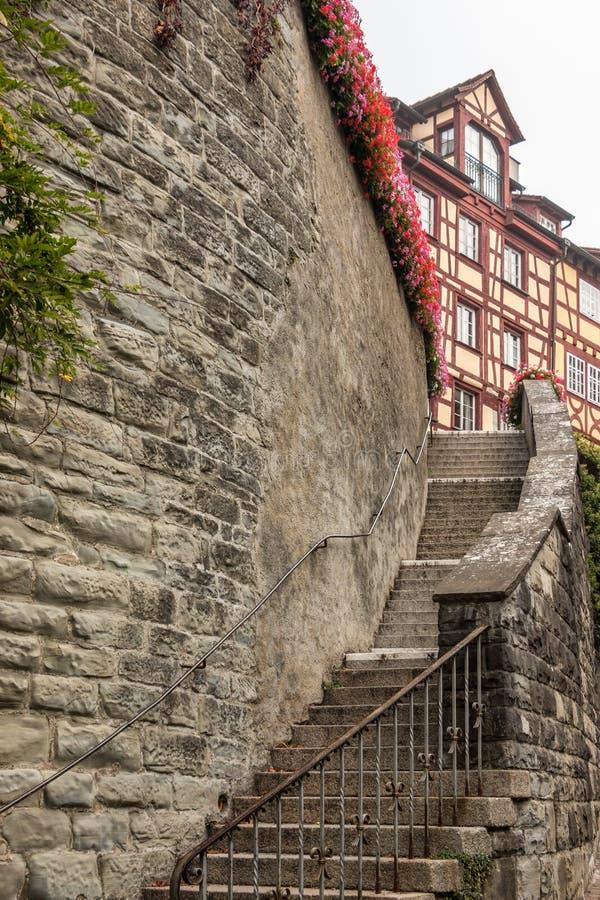 Haut mur en pierre avec un long escalier à quelques vieilles maisons médiévales photographie stock libre de droits