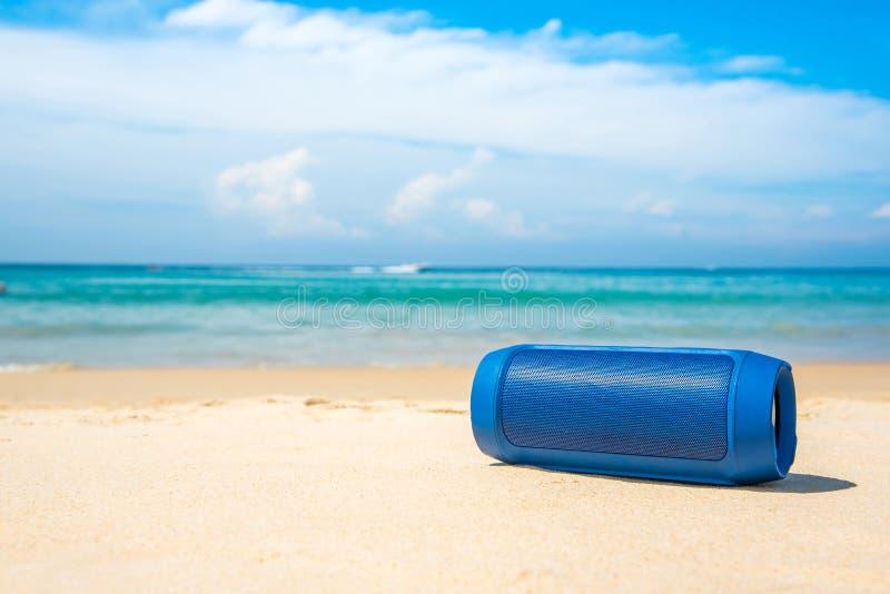 Haut-parleurs sans fil portatifs sur la plage et le ciel bleu photographie stock libre de droits
