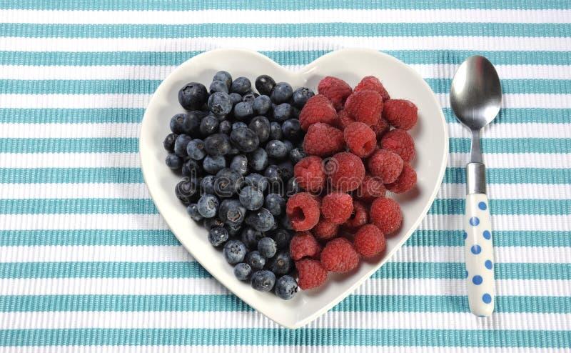 Haut petit déjeuner de fibre alimentaire d'alimentation saine avec des myrtilles et des framboises dans le plat de coeur image libre de droits