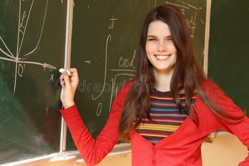 Haute accomplisseuse de belle fille de l'adolescence dans la salle de classe près du bureau s heureux photos stock
